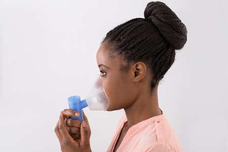 asma: Primer plano de la mujer africana joven que usa la m�scara de ox�geno