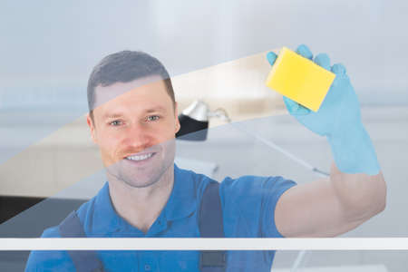 mid adult male: Mid adult male worker cleaning glass window with rag