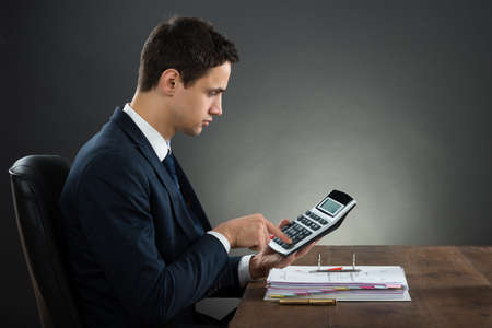 record: Side view of businessman using calculator while checking invoice at desk against gray background