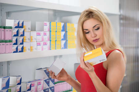 Beautiful young woman examining capsule packet at pharmacy