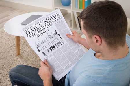 High angle view of mid adult man reading news on newspaper at home photo