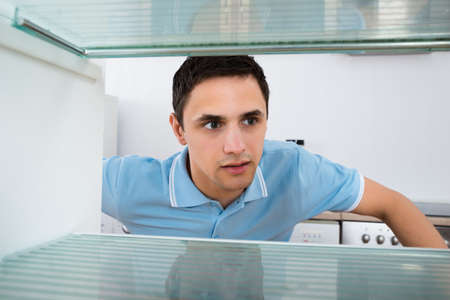 and the horizontal man: Shocked young man looking into empty refrigerator at home
