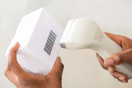 barcode scanner: Close-up Of Persons Hand Using Barcode Scanner To Scan A Barcode On Product Stock Photo