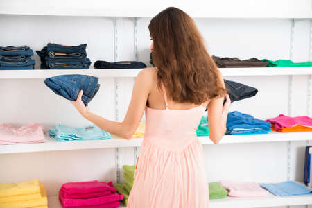 garments: Rear view of young woman choosing jeans in store