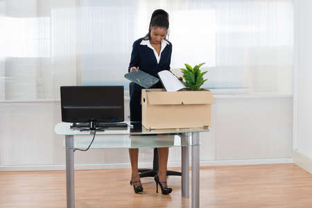 dismiss: Young African Businesswoman Putting Her Belongings In Box At Office Desk