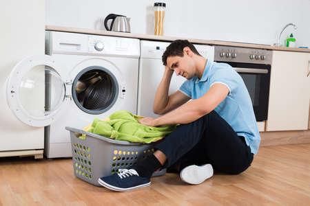 carga: joven tensado que mira la cesta de la ropa en el hogar