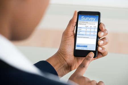 Primo piano di una imprenditrice di riempimento in linea Survey Form sul telefono mobile