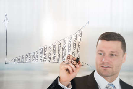 adult wall: Confident mid adult businessman drawing graph on glass wall in office