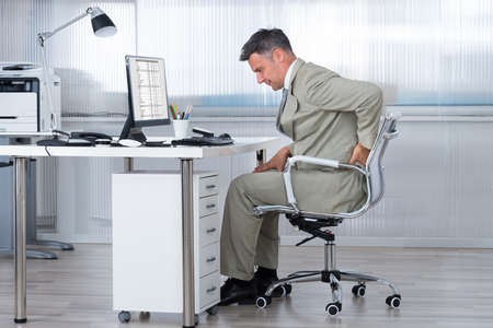 desk work: Side view of accountant suffering from back pain at desk in office