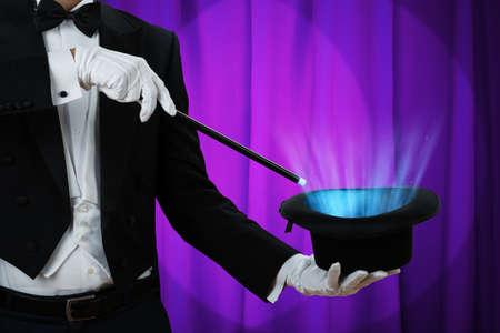 Sección media del mago que sostiene la varita mágica sobre el sombrero iluminado contra la cortina púrpura