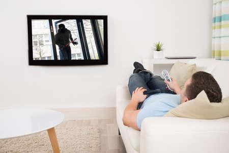 viendo television: Toda la longitud de hombre de mediana edad viendo la película en la televisión en la sala de estar Foto de archivo
