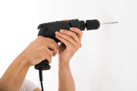 taladro: Imagen recortada de hombre joven que usa el taladro de potencia en la pared blanca en casa Foto de archivo