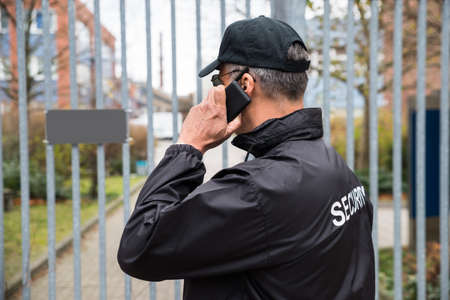 Confident mature security guard talking on mobile phone in front of gate