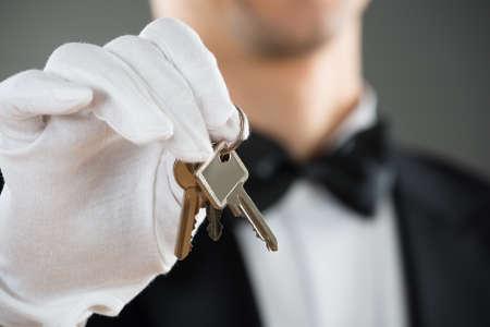 llaves: Sección media de camarero sosteniendo las claves contra el fondo gris