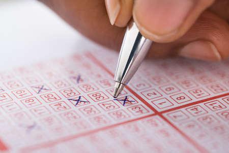 bingo: Primer plano de la mano de la persona Marcado de número en el billete de lotería con la pluma