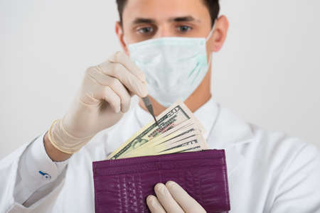 surgery expenses: Midsection of male surgeon removing banknote from wallet against white background Stock Photo