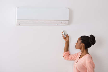 room air: Young African Woman Operating Air Conditioner With Remote Control