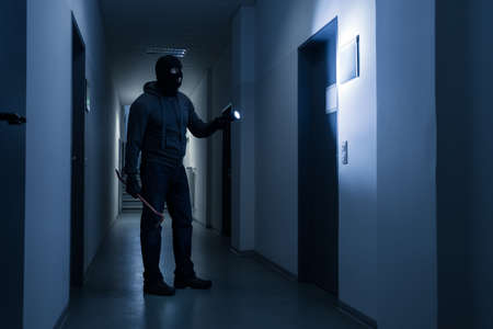 Volledige lengte van de inbreker met een zaklamp en breekijzer in het donker kantoorgebouw Stockfoto