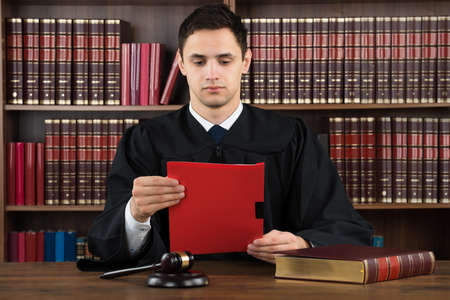Young male judge reading legal document at desk in courtroom