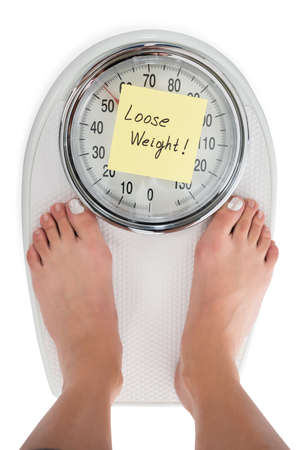 directly: Directly above shot of woman standing on weight scale with Loose Weight note