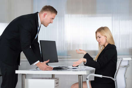 blaming: Young businessman blaming female employee at desk in office