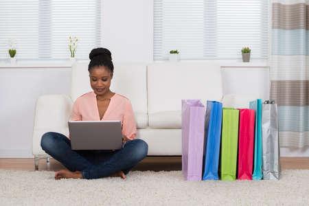 shopping: Mujer africana joven sentado sobre una alfombra compras en línea Foto de archivo