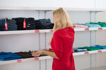 displayed: Rear view of confused woman gesturing while looking at clothes displayed in store