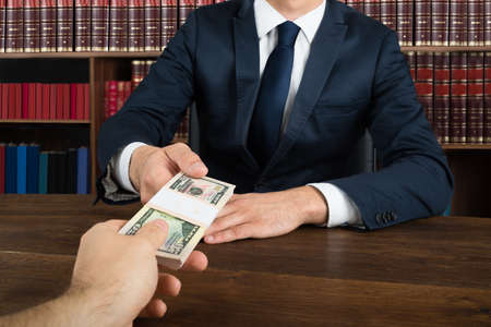 Midsection of lawyer taking bribe from client at desk in courtroom