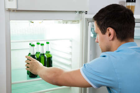tomando refresco: Side view of young man removing beer bottle from refrigerator at home
