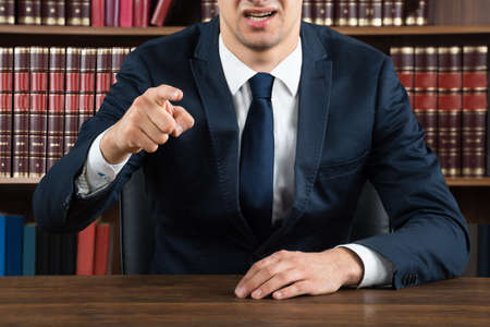 defenders: Midsection of male lawyer arguing while sitting at desk in courtroom Stock Photo