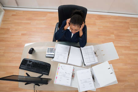 overworking: Overworking Frustrated Young Businesswoman At Office Desk Stock Photo