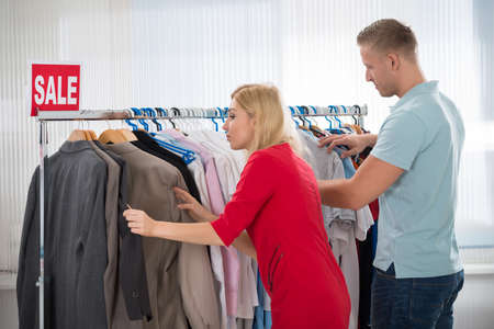 choosing clothes: Side view of man and woman choosing clothes in store Stock Photo