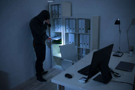 thievery: Robber with flashlight searching for documents in office at night Stock Photo