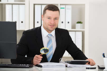 account executive: Male accountant analyzing invoice with magnifying glass at desk in office Stock Photo