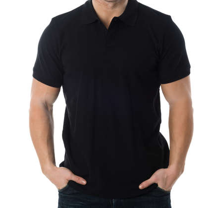 midsection: Midsection of man wearing blank black tshirt standing with hands in pockets against white background Stock Photo