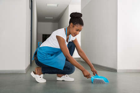 brooming: Young African Woman Sweeping Floor With Whisk Broom