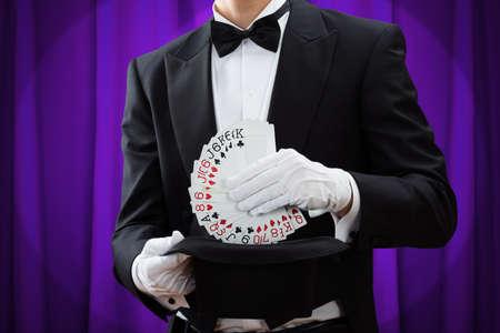 Sección media de mago hombre poniendo las cartas en el sombrero contra la cortina púrpura
