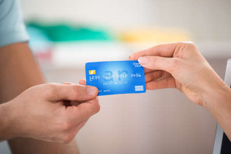 Cropped image of salesman taking credit card from female customer in clothing store