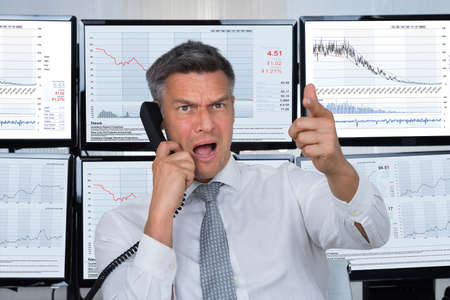 health equity: Angry male stock trader shouting while using telephone with computer screens in background Stock Photo
