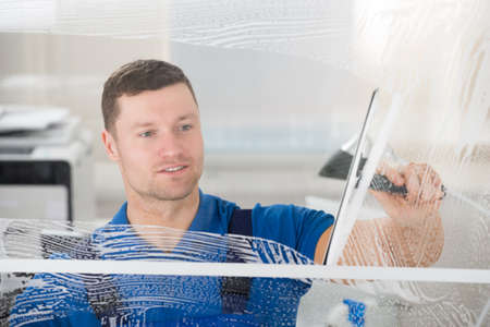 Smiling mid adult worker cleaning soap sud on glass window with squeegee