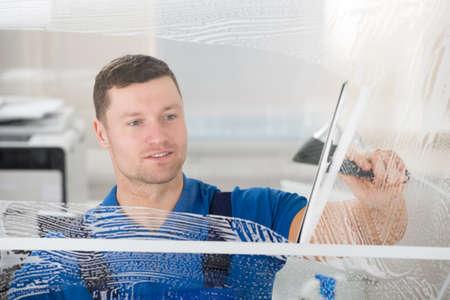 Sourire travailleur adulte mi savon de nettoyage sud sur la fenêtre en verre avec racle