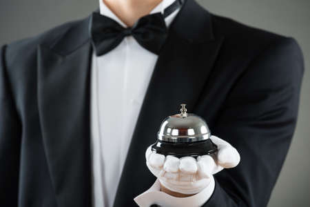 hospitality staff: Midsection of waiter holding service bell against gray background