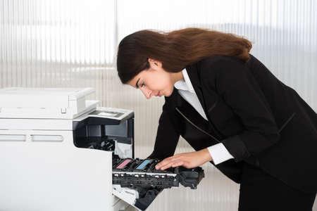 Vista lateral del cartucho de fijación de negocios joven en la fotocopiadora en la oficina