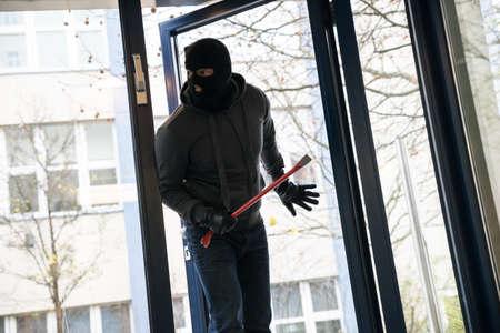 homme à capuche avec pied de biche entrant dans la maison