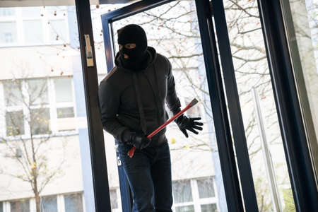 Hooded man with crowbar entering into house