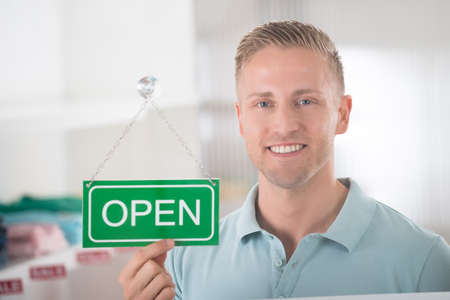 store sign: Portrait of confident male owner holding open sign in clothing store