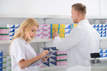 Male and female pharmacists checking inventory at pharmacy Stock Photo