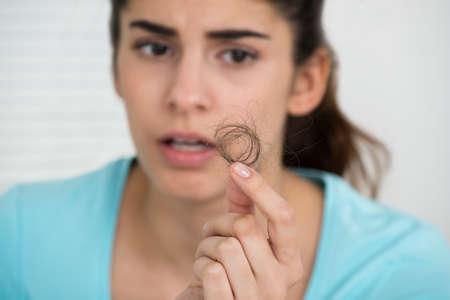 expresiones faciales: mujer joven sorprendido mirando a la caída del cabello