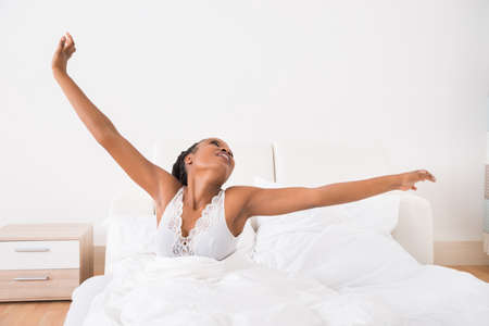 gente durmiendo: Retrato de una mujer africana joven que estira sus brazos en cama