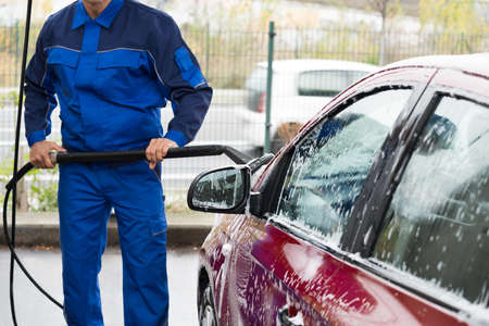 Midsection of serviceman washing car with scrubbing brush at service station
